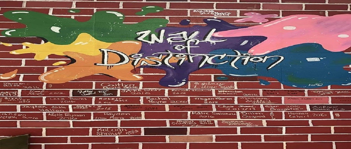Picture of a wall painted to look like a brick wall that has been signed by students.